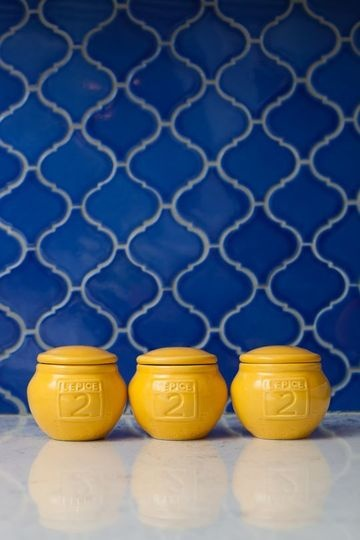 Retro signal-blue & white 70's type tile on wall, with 3 traffic-yellow pots in front.