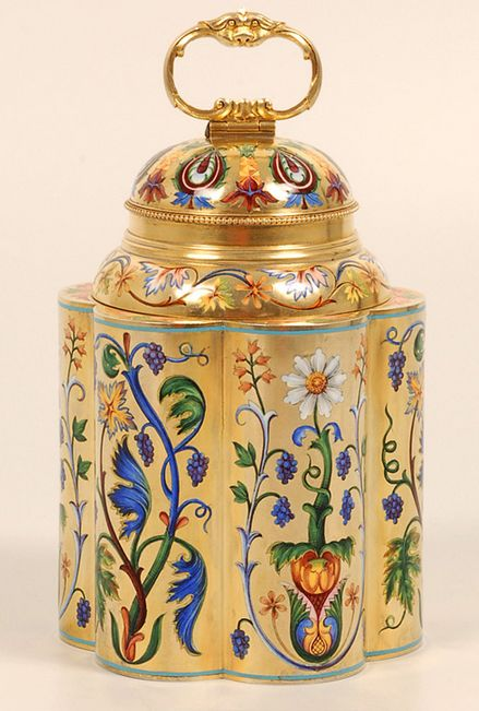 A magnificent and exceptionly rare Russian silver gilt and shaded champleve enamel tea caddy by Ivan Khlebnikov, Moscow, 1896-1908. The six, cylindrical lobed sides beautifully decorated in various alternating multi-color scrolling floral and foliate motifs against a matte gilt ground, the double-domed lid similarly worked with floral designs and paisley motifs between stylized pineapples. From John Atzbach.