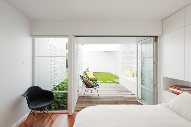 Prineas Architects. The main bedroom opens onto a decked space, cleverly bounded by white breezeblock walls.