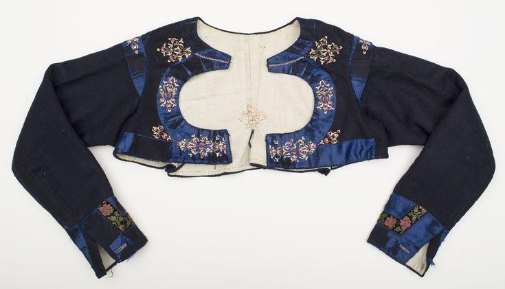 Kvinnotröja i blått kläde fodrad med oblekt linne. Dekorerad med blå sidenband kring ärmslut, hals-och framkanter och axelkarmarna. Broderier i plattsöm på det blå sidenbandet och även mitt bak på klädet. Kring ärmsluten är där också ett blommönstrat sammetsband och handsytt knapphål. Fodrad med linnetyg. Tröjan har cirkelformad utskärning mitt fram, typisk för sydöstra Skåne.