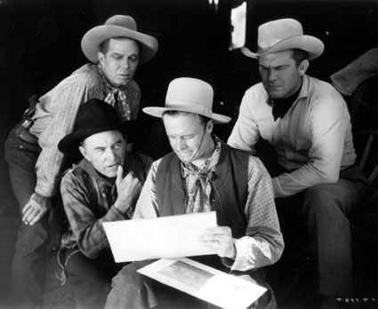 POWDERSMOKE RANGE (1935) - Hoot Gibson - Harry Carey - Guinn 'Big Boy' Williams are attentive while Hal Taliaferro examines legal documents pertaining to missing cattle stolen from them - Directed by Norman Fox - Based on the 'Three Mesquiteers' novel by William Colt MacDonald - RKO-Radio - Publicity Still.