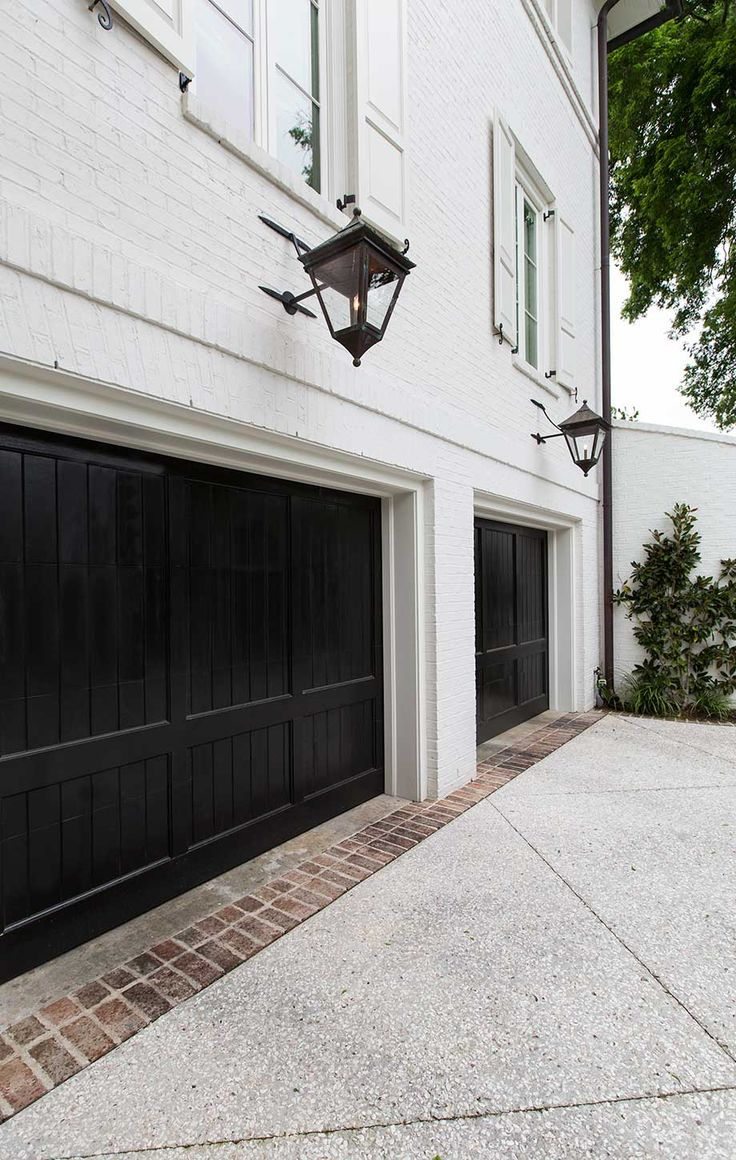 Double black garage doors white brick uec fixtures architecture outdoor spaces pinterest for Exterior garage doors
