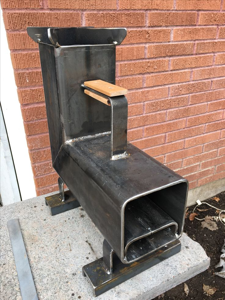 "Just finished building my first rocket stove. All parts are made from cutting the same 5 1/2"" square tubing into different parts,except for the feet. Then I used some metal washers and scrap cherry wood create a handle so I could move it around even when it was hot."