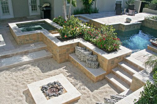 I LOVE THE SAND AROUND THE FIRE PIT! I can feel my toes in it now:) Findley's design features an asymmetrical arrangement of pool, spa and conversation grotto linked by shallow canals.