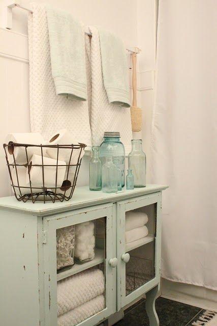 Patinar la cajonera verde (que está en el living) de color blanco o celestito y llevarla al baño, abajo del estante. Guardar toallas, secador de pelo, papel, toallitas, etc, (Todo lo que no da que se vea en uno o dos estantes que irían arriba).