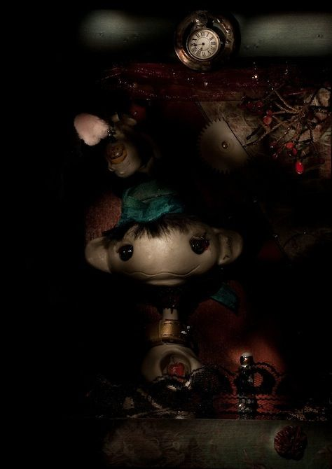 Hobo Josy, certainly richer than the Sheikh (Mona Mae): OOAK artwork captured in still life torchlight photo - work itself uses mix of materials - porcelain  clay, glass eyes, fabric for dolls, metal parts made by artist - background as glass, fusing, metal work, soldered pieces, etc., etc.