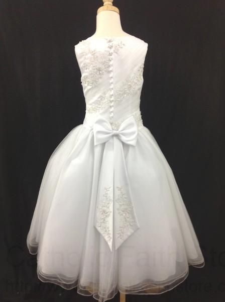 (4 Tea Length, White) This sleeveless First Communion dress features beautiful asymmetrical diagonal sections on the bodice alternating heavy floral pearl beaded appliques with sheer ruched areas. The back of the dress is a mirror image of the front but has lovely faux satin covered buttons that hide the zipper closure and an elegant bow accented with matching floral pearl beaded accents at the tips. The dress is paired with a puckered princess style sheer overlay skirt. From the Angel ...