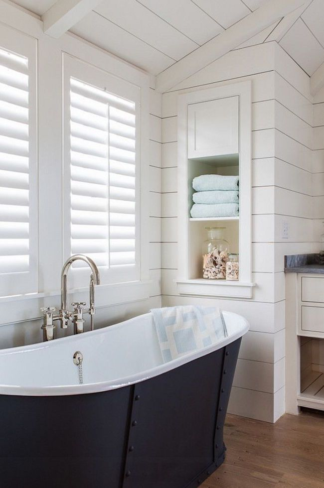 Bathroom with shiplap walls and built-in storage shelving near freestanding bathtub