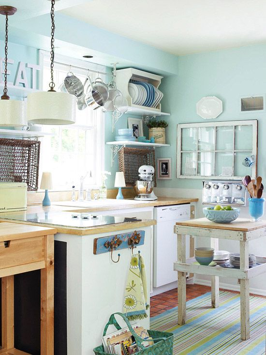 Like lots about this kitchen space. I could make that island bench myself! Love the hooks at the end of the bench. And those pans hanging from the rack above the sink - too cute!