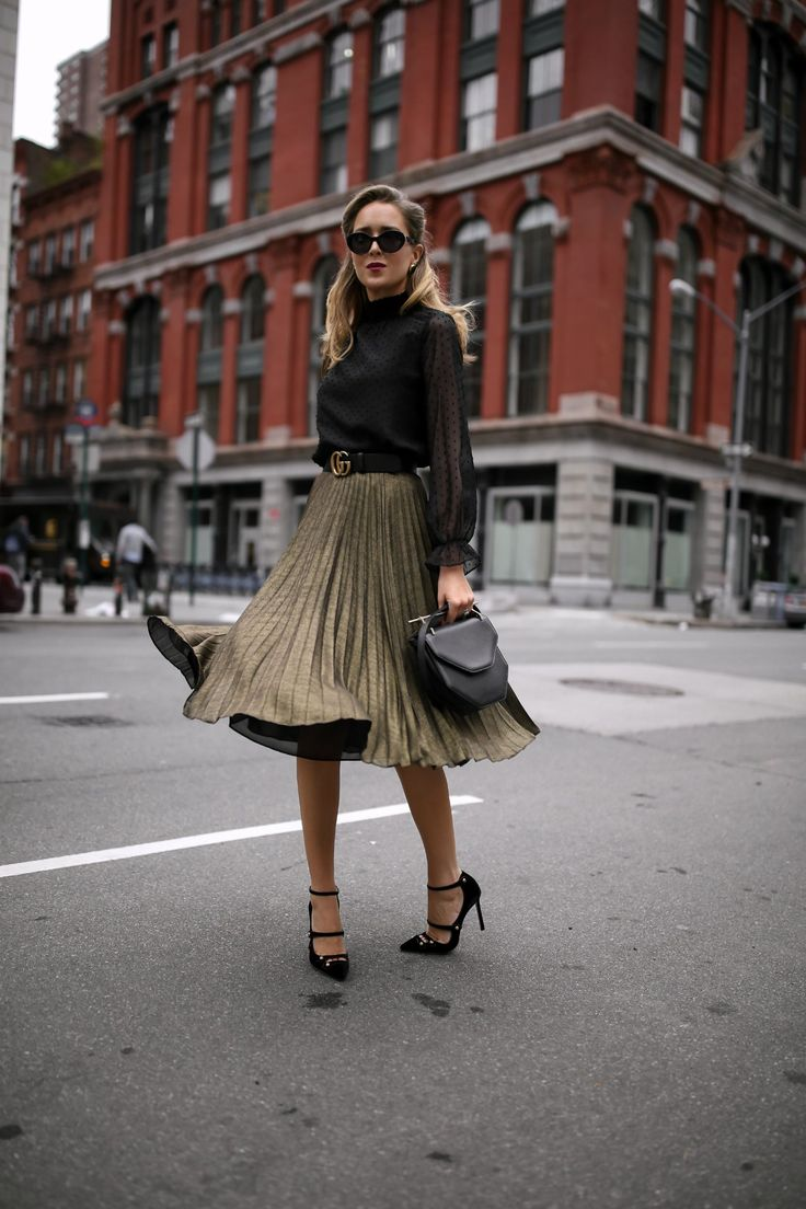 Mary Orton wears a Hobbs London metallic pleated midi skirt, a black Aqua mock neck blouse with Swiss-dot detailing, a black leather Gucci waist belt, strappy Mary Jane pumps, a black structured M2Malletier handbag and black cat eye sunglasses