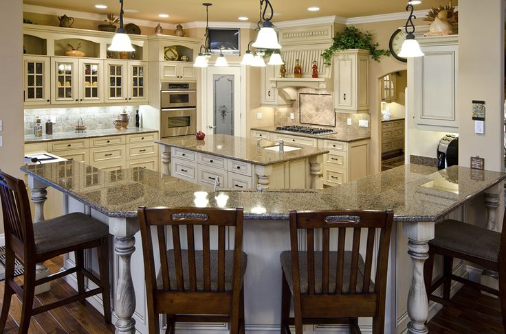 Across a large kitchen stuffed with detailed features, we see a pair of a wildly different islands. The first is a C-shaped expanse with two tiers of granite countertop for both utility and in-kitchen dining purposes. The second is a traditional rectangular island with built-in sink. The ornate distressed white wood cabinetry brings a hint of rustic charm to the space, while beige tile backsplashes mix in effortlessly. Stainless steel appliances add a final dash of complexity.