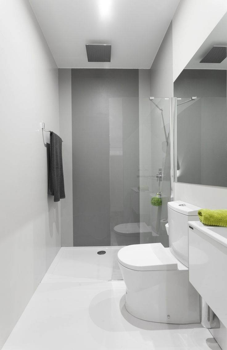 Narrow bathroom with Sanindusa products. Small size toilet and basin. Well organized space with gray and green decoration