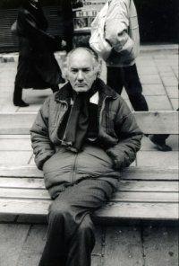 """Il grande scrittore austriaco Thomas Bernhard (1931-1989) è seduto su una panchina della zona pedonale di Vienna del Graben, luogo delle sue passeggiate. Non solo la panchina ricorre  in alcune narrazioni di Bernhard, ma è l'intera sua opera ad essere scritta come se egli fosse sempre seduto su di una panca posta sulla vetta di una montagna. Da lì lo scrittore osserva lo squallido spettacolo della """"stupidità della popolazione austriaca"""", l'oggetto preferito delle sue feroci invettive."""
