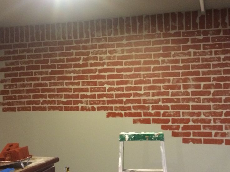 Faux brick wall in progress. Painted wall grey, then used dollar store car washing sponges to sponge on the red. Valspar wet pavement for base and French quarter for brick color.