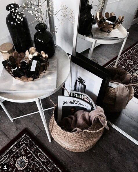 Table by the window with basket for utensils. Mirror leaning against wall next to hand