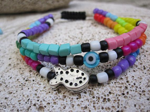 3 in 1 seed beads bracelet with evil eye and metal fish for good luck :) Adjustable size one size fits all, with macrame .  Summer sale offer :) Rainbow fish and evil eye for good luck with white waxed cord and black macrame finish   Visit my shop for more little things https://www.etsy.com/shop/MykonosByBoni