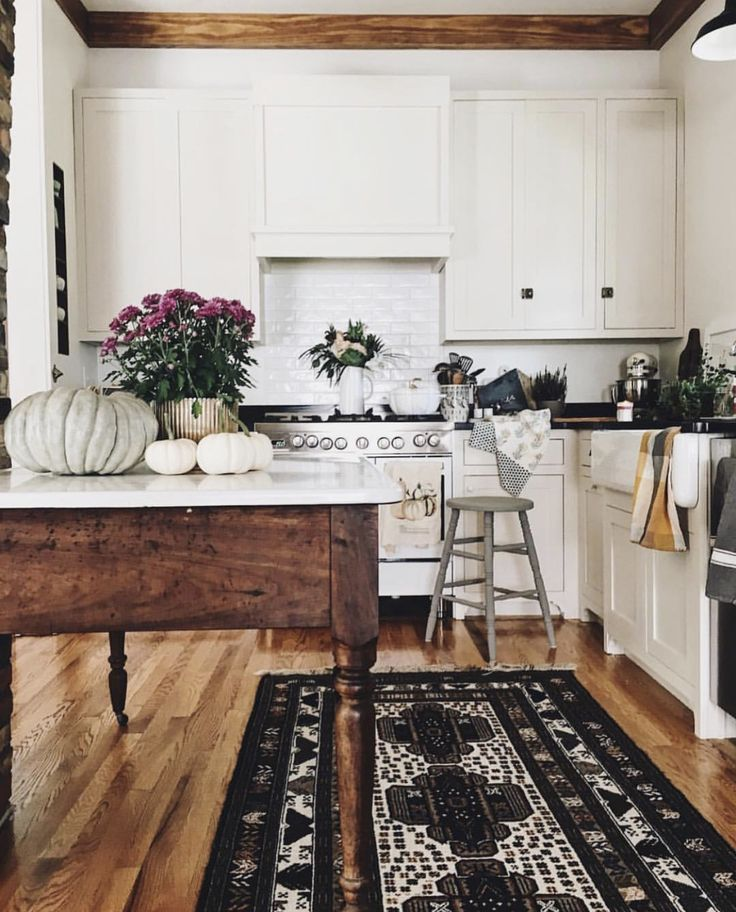 Kitchen. white cabinets. white subway tile. darkwood table. wood accents. mums.