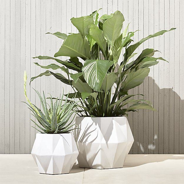$40 Shop isla small white geometric planter. Handmade from natural clay, earthenware angles form diamond-like facets from rounded base to tapered top. Glossy white finish is the effect of a reactive glazing technique that makes each vase unique.