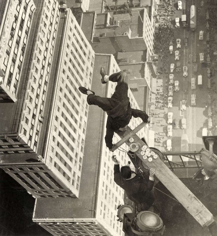 A man balancing on a piece of wood on the roof of a skyscraper 1939