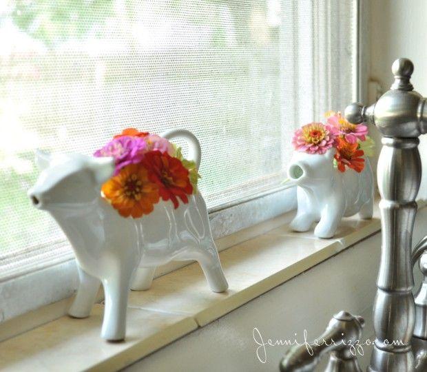 vintage cow creamers with flower brighten a kitchen window