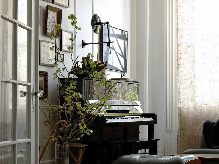 Another perspective of the upright piano, framed art, elbow lamp and light from window diffused through linen shades