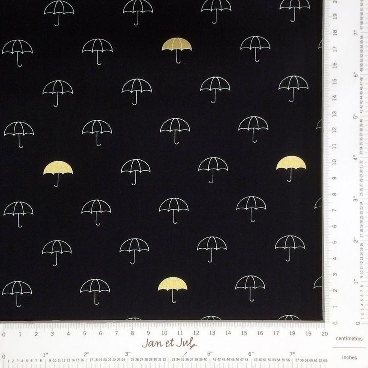 Fantástica tela negra con paraguas mini y una paragua en color oro o mostaza. Es una tela divertida, con dibujos pequeños, moderna y muy actual.