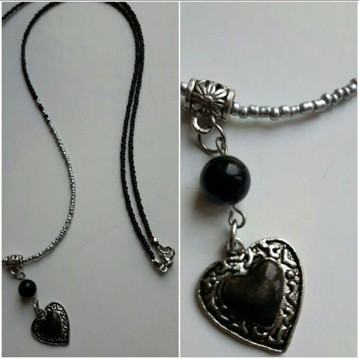 Lange ketting van zwarte en zilveren  rocailles  ( kleine glaskraaltjes). Hanger van DQ metalen hart en zwarte glaskraal aan bails.