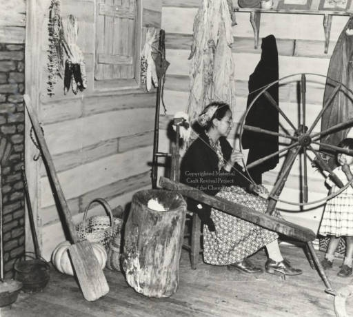 woman + child | spinning | Cherokee Reservation, North Carolina, U.S.A. | undated | also note: two baskets: one of white oak to the left of the large log mortar + one of rivercane, woven in the Noonday Sun pattern, behind the young girl