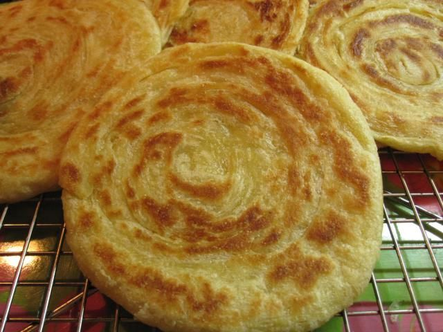 Meloui are round Moroccan pancakes (rghaif) that are shaped by rolling a strip of dough up like a rug, and then flattening the upright coil into a circle. They can be eaten plain or with syrup made from butter and honey.