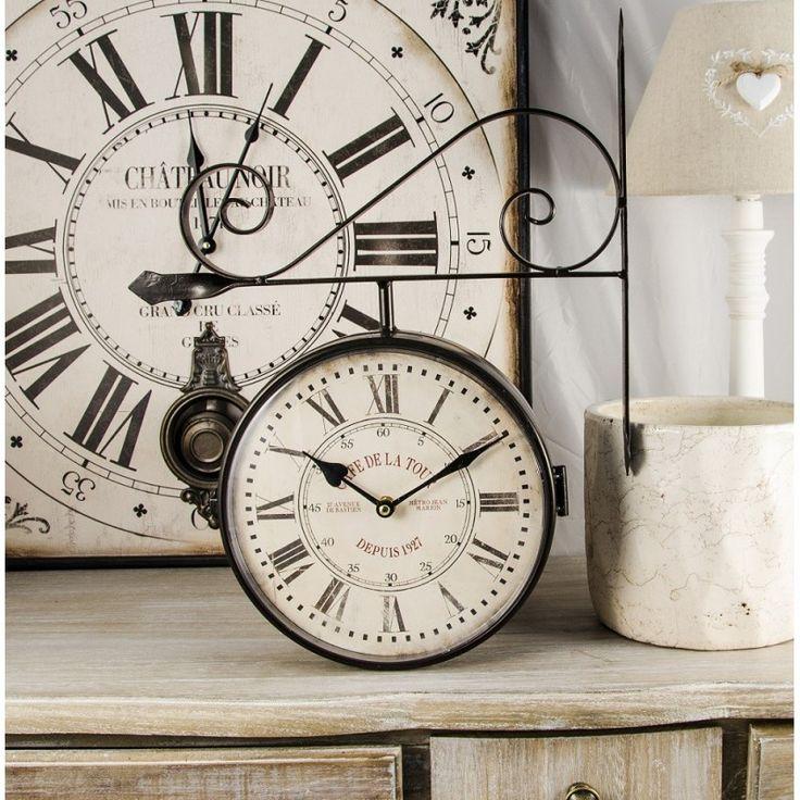 Zegar dworcowy o białej tarczy z czarnymi rzymskimi cyframi, ozdobiony metalową konstrukcją. Doskonała dekoracja w starym stylu.