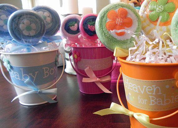 Washcloth Lollipop Pail - buy a cheap metal pail, wrap a cute label around it and a bow on the handle, fill it with shredded paper and add flowers made from washcloths. These would make great centerpieces for a baby shower.