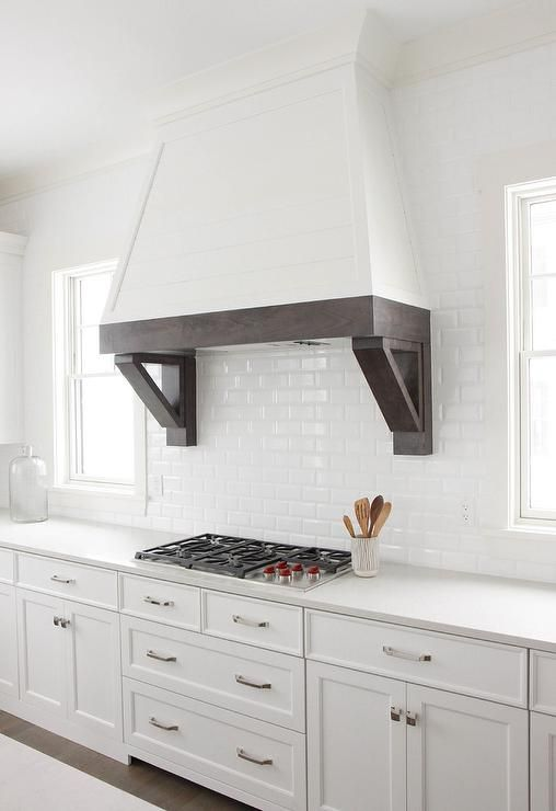 Between windows, a white shiplap hood fitted with an espresso stained trim and corbels is fixed to all white mini subway backsplash tiles above an integrated cooktop mounted to a white quartz countertop above white pot and pan drawers donning polished nickel pulls.