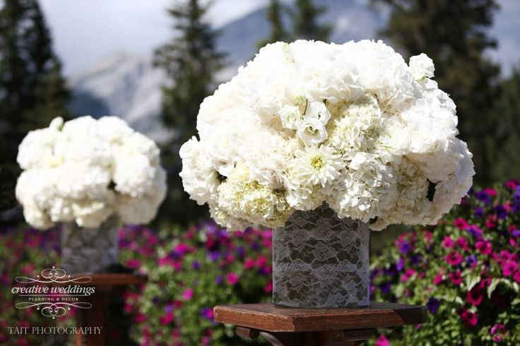 Wedding ceremony arrangements on the Outdoor Terrace at the Fairmont Banff Springs using white hydrangea, white lisianthus, white mums and white roses in lace-wrapped cylindrical vases. (Photo courtesy of Tait Photography)