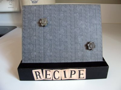 recipe holder:  metal board covered in scrapbook paper held up by a grooved wooden block.  you just use the magnet to hold your recipe card in place.