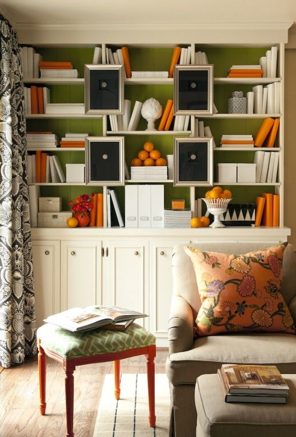 White painted bookshelves with green backs and orange accessories