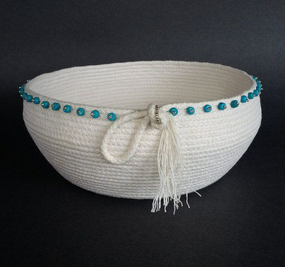 I enjoy exploring different shapes and fabrics for making baskets and I decided to try some without wrapping fabric around the cord. I think the finished piece here is serene and quiet in its beauty. The lack of print or color makes the subtle shape more noticeable. The top coil ends in a soft knot with a frayed tassel. Silver seed beads and turquoise wooden beads are hand sewn around the rim. The basket is 4 inches deep and 8 inches in diameter. FREE SHIPPIMG