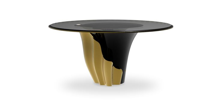 Yasmine  is a modern dining table fashioned with smoked glass and mounted on a solid wooden base. The combination black and gold brings an modern design.