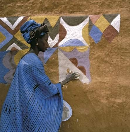 A Soninke woman paints the wall of her house in Djajibine, Mauritania