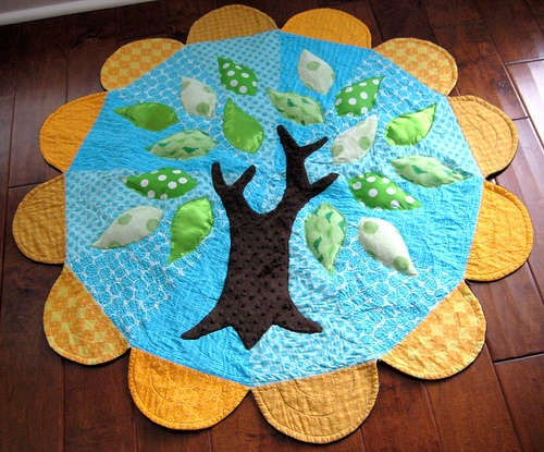 Baby play mat. Ok, ok, I don't have a baby - but I plan on making this for my apartment (or something similar). It's just so cute!   Materials: Main fabric, border fabric, backing fabric, leaf fabric, tree fabric, sewing machine and materials