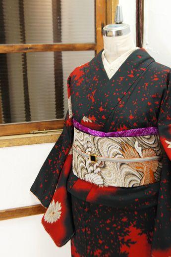 黒と赤のコントラスト美しく織り出された草花のシルエットに、白い菊花がふわりと浮かぶ正絹御召の袷着物です。