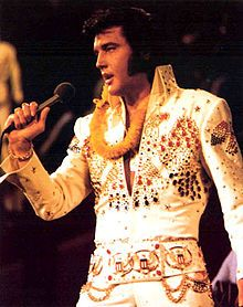 Elvis sings into a handheld microphone. A golden lei is draped around his neck, and he wears a high-collared white jumpsuit resplendent with red, blue, and gold bangles.