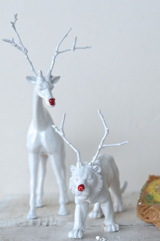 Plastic toys with twigs glued on heads as antlers, spray paint white and dab some red paid or red glitter on the nose
