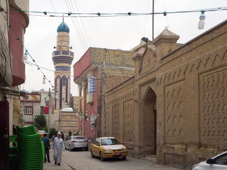 The wall of the Armenian church compound stands on a Basra street dominated by a minaret.