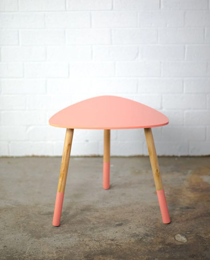 This handcrafted side table comes in a fun triangular shape with paint dipped timber legs