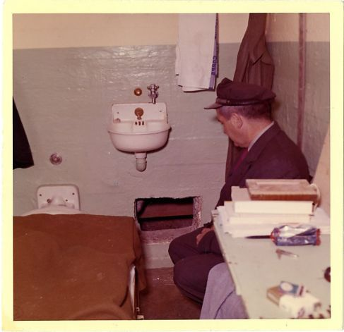 This 1962 photo from the U.S. Penitentiary Alcatraz shows Frank Morris's cell and Senior Officer Howard Waldron looking at the point of escape