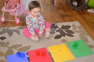 1.Cognitive Development and Physical Health and Well Being 2.CD The older  infant explores and manipulates objects with different shapes and sizes sometimes fitting shapes into place. This activity help children to use simple house held items to use fine motor skills and color recognition.