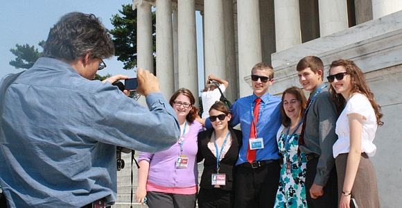 Students at the Youth Education Summit take photos in front of the Jefferson Memorial