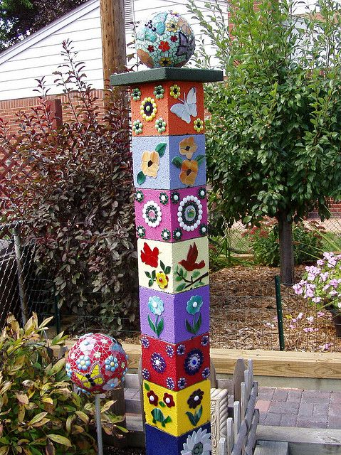 "decorated cement blocks. Artist wrote this: ""Tower with gazing ball topper  I painted and stacked 9 concrete blocks and topped it off with a mosaiced bowling ball."""