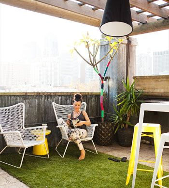 Artificial turf laid on the rooftop to make it more like a garden. She wrapped fabric from local fashion houses around her frangipani tree for year-round colour! The armchairs are from Ikea