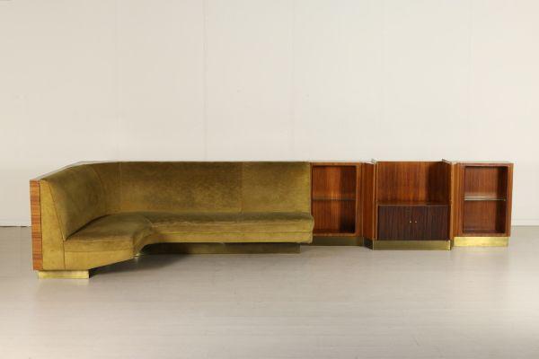 Grande divano ad angolo con mobile collegato; imbottitura a molle, rivestimento in velluto, legno impiallacciato palissandro, fascia in ottone. Buone condizioni, presenta segni di usura sul rivestimento.